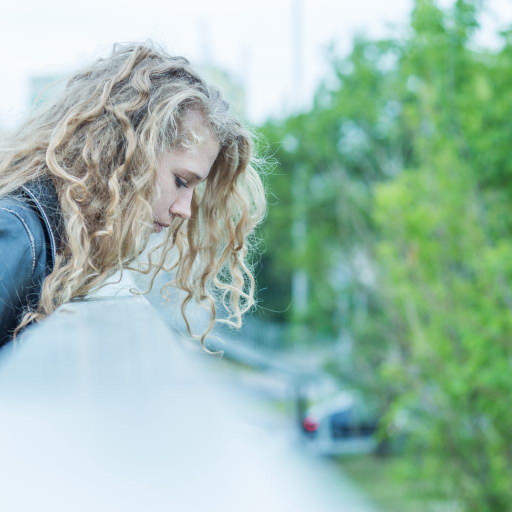 Image of depressed woman standing on the edge of bridge
