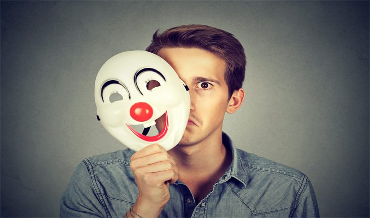 Man with sad face with laughing clown mask